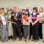 Homemakers A+ Adult Day Service President Scott Bradshaw cuts the ceremonial ribbon to open the business during a Starke County Chamber of Commerce ribbon cutting ceremony.