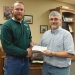Darrell Marks, energy advisor for Kankakee Valley REMC, presents a check to Mark Bailey, owner of Bailey's Discount Center.