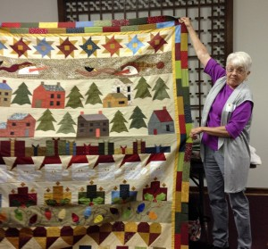 "Speaker Joyce Lawyer shows one of her many quilts she spoke about during her program, ""Around the Block."""