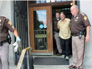 Deputies from the Marion County Sheriff's Office lead Richard Dobeski, 67, out of an Indianapolis library. Photo provided by the LaPorte County Sheriff's Office.