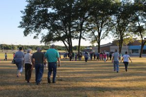 School board meeting attendees walk from the administration building to the high school. The meeting was moved after North Judson Police raised safety concerns due to the overflow crowd.